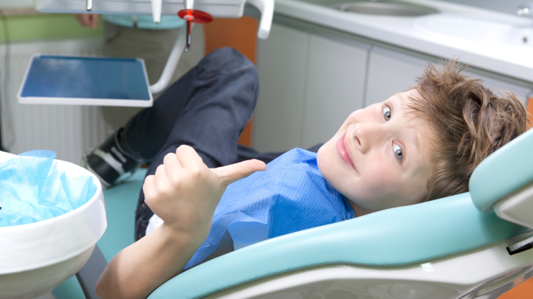 A Boy Gives A Thumbs-Up in A Dental Chair | Medina, Ohio Children's Dentistry