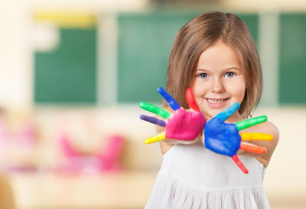 A child shows her painted hands to the camera | Medina OH Children's Dentist