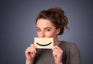 A Woman holds a smile sign in front of her mouth | Medina Dental Bridges