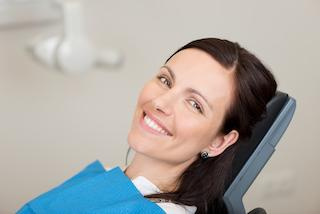 A woman smiles in the dental chair | Medina OH Same-Day Crowns
