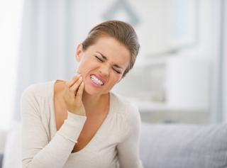 A woman holds her jaw in pain | Emergency Dental Care Medina OH