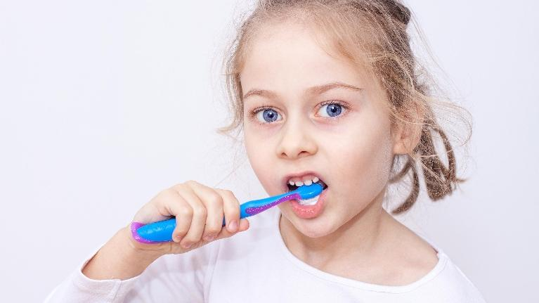 A girl brushes her teeth | Medina pediatric dentist