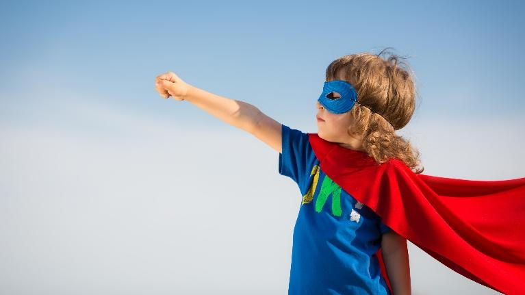 a child with a cape on stands in the wind | Medina OH Children's dentist