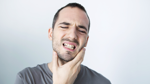 Man Holding Jaw From Toothache